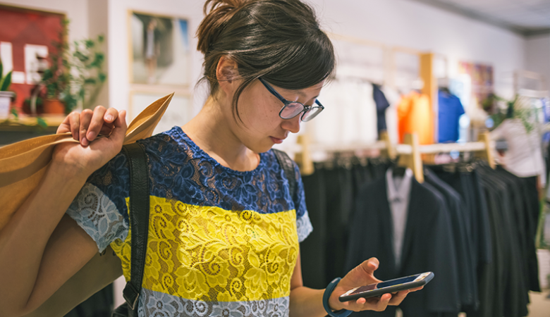 Young woman checking phone after making a purchase
