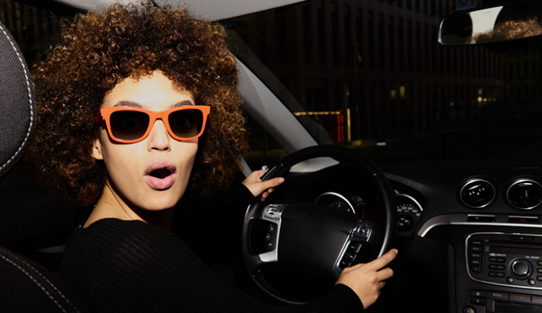 Young woman in new car with orange sunglasses