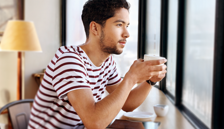 Young man staring out coffee shop window