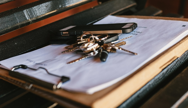 Keys on top of a clipboard with paperwork