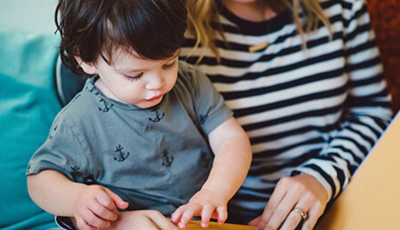 Toddler in blue shirt sitting with his mom