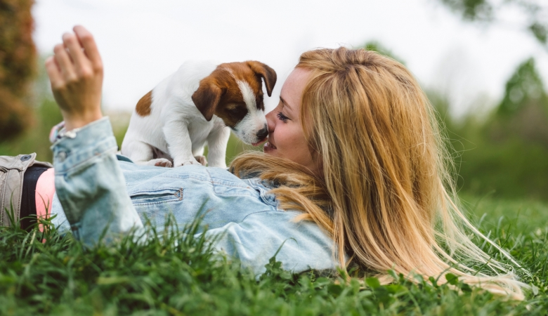 Woman laying in grass with puppy on top of her licking her face