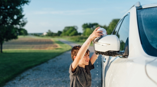 Boy washing white car in the sunshine