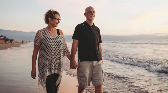 Couple in their 50's walking on the beach at sunset