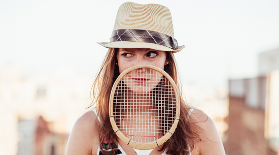 Girl in a fedora holding a racket
