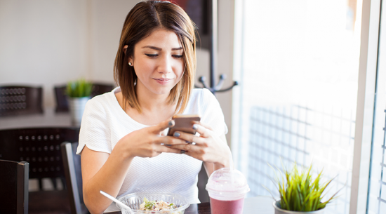 Woman using smartphone while having lunch